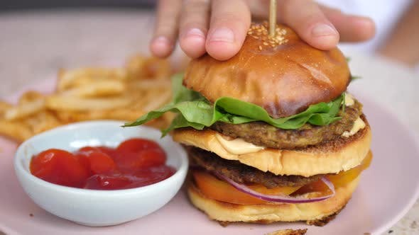 A Hand Fixing a Bun of the Plant Based Double Decker Burger