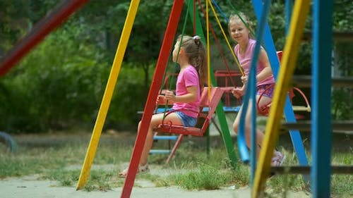 Two girls ride a swing in the Park on a Playground on a summer day.