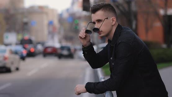 Junger Mann stützt sich auf Barrieren Blickt auf den Stadtverkehr