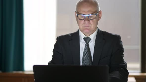 Thumbnail for Happy Senior Businessman Using Phone And Laptop While Sitting In The Office