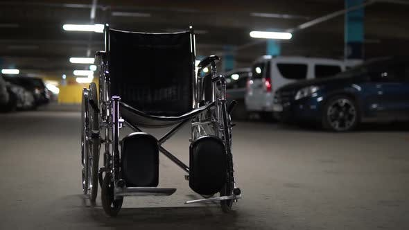 Thumbnail for An Empty Wheelchair Stands in the Middle of a Car Park. Wheelchair Is Standing on the Road