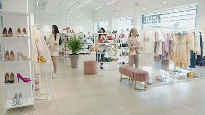 Group of Women Walking in Shop Looking for Clothing Touching Garments Enjoying Shopping