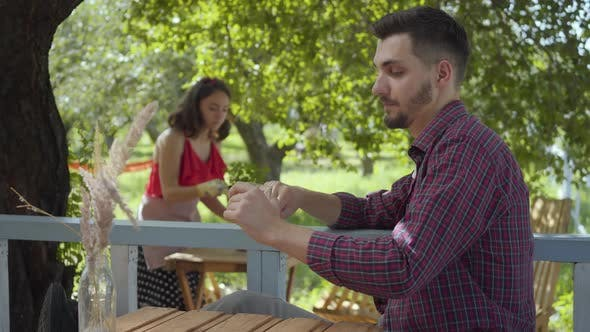 Thumbnail for Young Bearded Man Drinking Tea in the Foreground While Attractive Girl in Retro Clothes Planting
