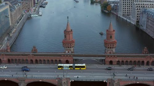 Oberbaum Bridge in Berlin, Germany and Yellow Bus Passing Over Spree River in Daylight, Aerial Tilt
