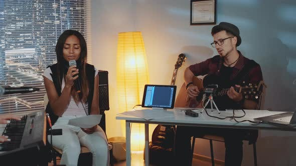 Thumbnail for Modern Band Rehearsing in Home Studio: Young Man Playing Guitar and Mixed-race Girl Singing Into