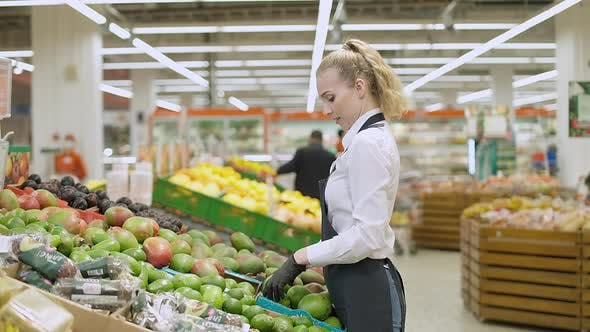 Female Store Employee Puts Mango Fruits on a Shelf in an Organic Store Young Woman Replenishes