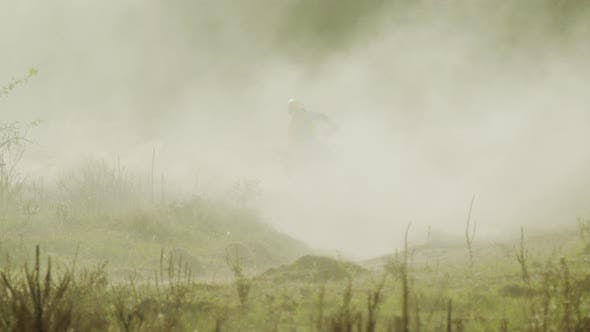 Thumbnail for Rider on a motocross driving through dust