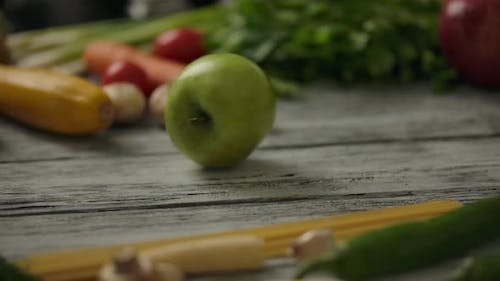 Crop Person Rolling Apple on Table