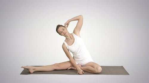 Beautiful Young Woman Wearing White Clothing Doing Yoga Exercise Sitting in One-Legged King Pigeon