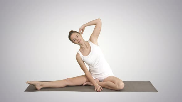 Thumbnail for Beautiful Young Woman Wearing White Clothing Doing Yoga Exercise Sitting in One-Legged King Pigeon