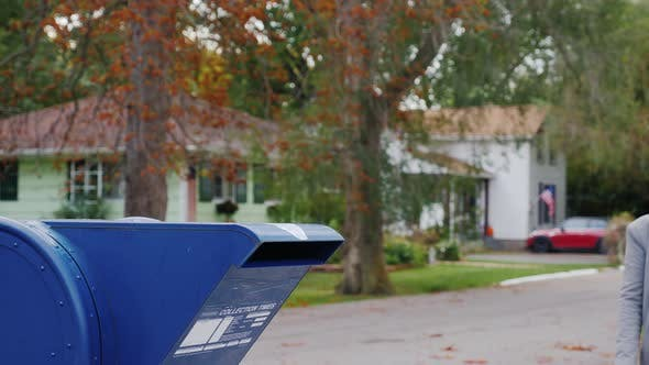 Thumbnail for A Woman with a Dog in Her Arms Approaches a Mail Box on the Street and Throws a Letter Into It