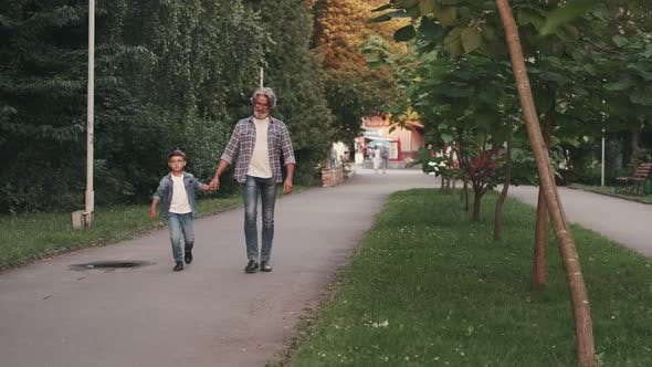 Thumbnail for Hippie Grandfather and Boy Walking in the Park Holding Hands