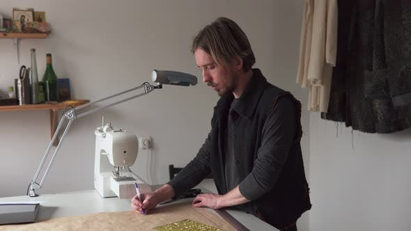 Man Designer Drawing Creative Clothing Pattern While Working in Workshop