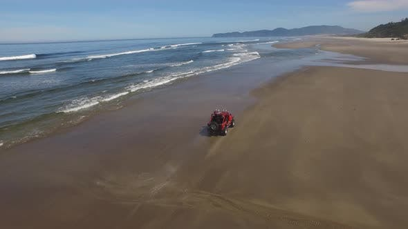 Aerial shot of 4x4 off road vehicle driving on beach