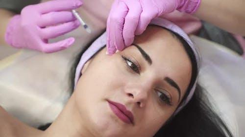 Eine Frau über das Verfahren von Injektionen in einer Kosmetologie-Klinik