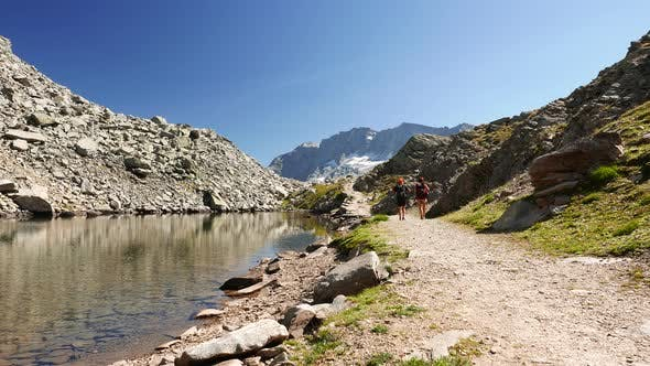 Couple hiking on mountain top in high altitude rocky landscape and alpine lake