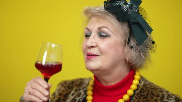 Thumbnail for Closeup of Carefree Senior Rich Woman Smelling and Drinking Red Wine From Wineglass