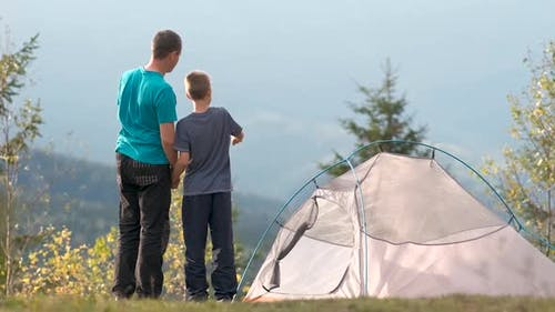 Young father with his child son resting together near a hiker tent in summer mountains. Active