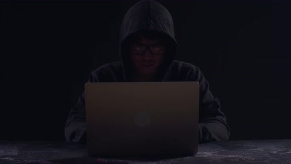 Asian Male Hacker Using Laptop Computer Hacking With Dark Background