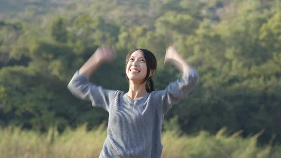 Thumbnail for Excited woman raising hand up at outdoor