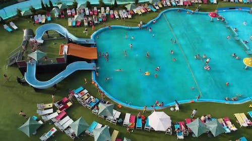 People swim and have fun in the large pool at the water park.