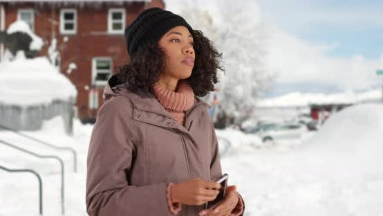 Cover Image for Pretty black female removes gloves to text on cell phone outside in the snow