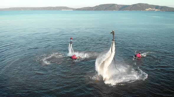 Cover Image for Sportive Men Doing Tricks with Jet Packs Over Sea Water