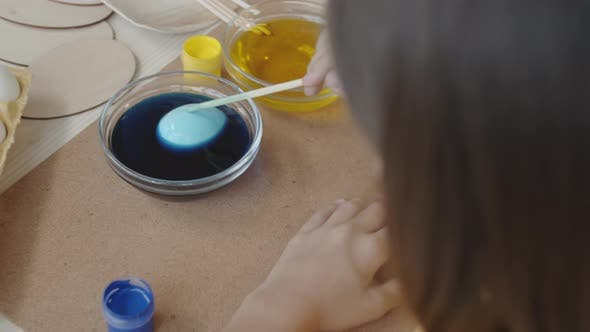 Thumbnail for Girl Dipping Easter Egg in Blue Food Coloring