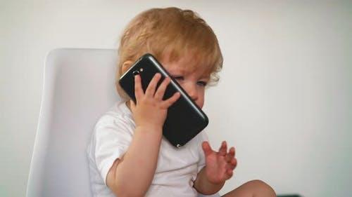 Kleinkind Blonde versucht großes Smartphone zu nehmen
