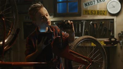 Teen Boy Repairs Bicycle