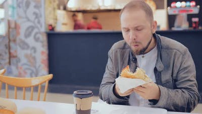 Man Eating a Burger in a Fast Food Cafe