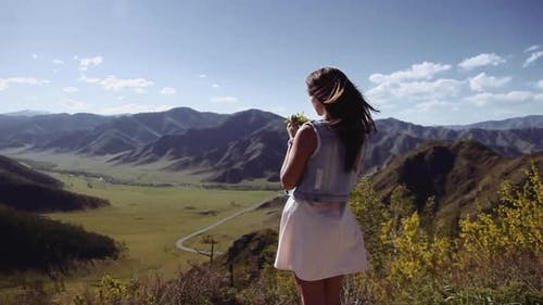 A Beautiful Girl Stands on a Cliff in the Mountains and Holds a Bouquet with Flowers