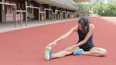 Woman stretching legs in Sport running track