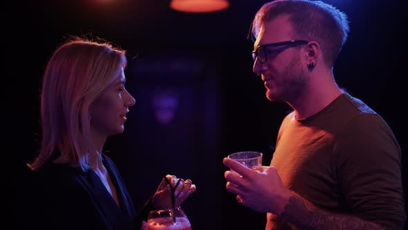 Thumbnail for Adult Couple Drink Cocktails in the Bar. Man in Glasses and Blond Woman Talking at the Disco