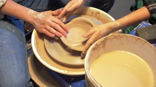 Thumbnail for Woman and Boy Make Plate on Pottery Wheel in Workshop