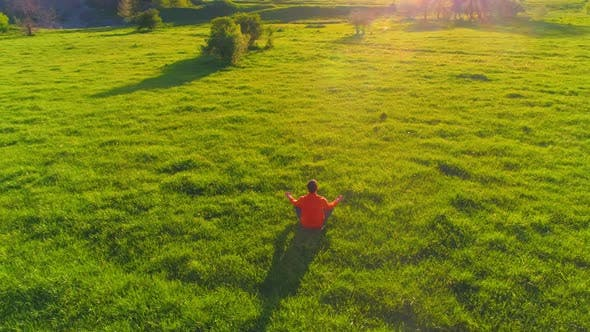 Cover Image for Low Altitude Radial Flight Over Sport Yoga Man at Perfect Green Grass. Sunset in Mountain.