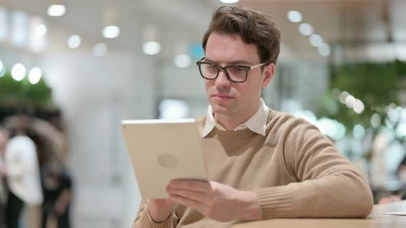 Young Male Designer Using Tablet in Office