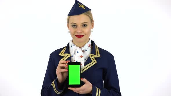 Thumbnail for A Young Stewardess Holds a Smartphone with a Green Screen and Smiles at the Camera - White Screen