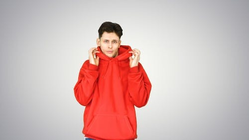 Casual man in red hoody dancing on gradient background.