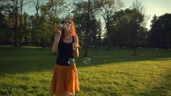 Thumbnail for Beautiful Young Redhair Girl Blowing Soap Bubbles Outdoors. Sunset