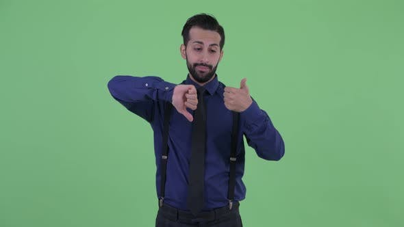Thumbnail for Confused Young Bearded Persian Businessman Choosing Between Thumbs Up and Thumbs Down