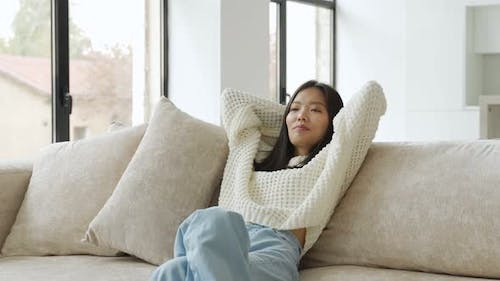 Beautiful Young Asian Woman in a Sweatshirt Resting on the Sofa in the Living Room Throws Her Hands