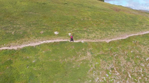 Thumbnail for Aerial View of a Traveler with Backpack Climbing Along Mountain Slope. Epic Shot