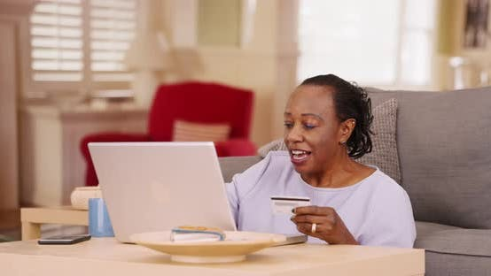 Thumbnail for An older African American woman uses her credit card and laptop to do some online shopping