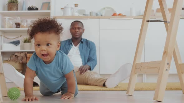 Thumbnail for African Man Watching Child Crawling