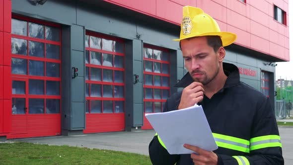 Thumbnail for A Young Firefighter Reads Papers, a Fire Station in the Background