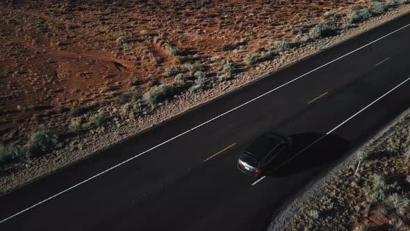 Thumbnail for Drone Follows Silver Minivan Car Moving Along Incredible American Desert Highway Road with Beautiful