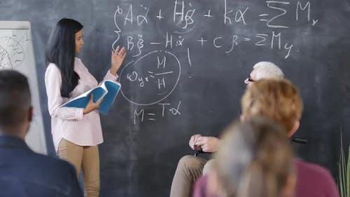 Student versucht, Gleichungen auf Tafel zu erklären