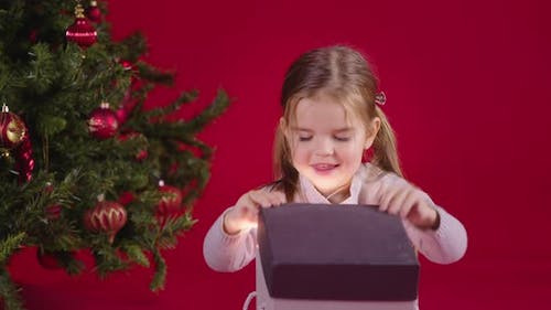 Christmas Miracle. Happy Little Girl Opening Xmas Gift with Magic Light Inside