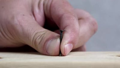Person holding nail in place as they hammer it